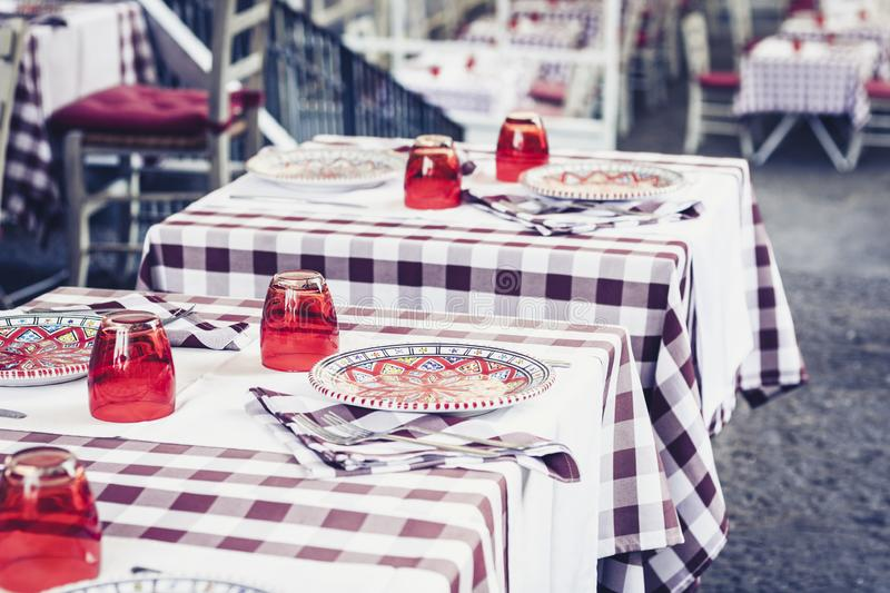 Serving on the table in the restaurant in Catania, Sicily, Italy: plates, glasses and napkins.  stock photo
