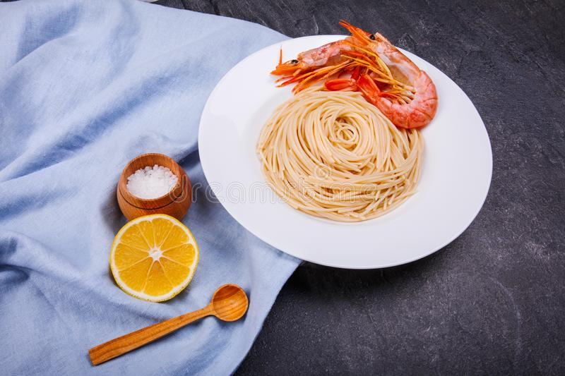 On the table is spaghetti with royal prawns, slice of lemon and a salt-pot. royalty free stock image