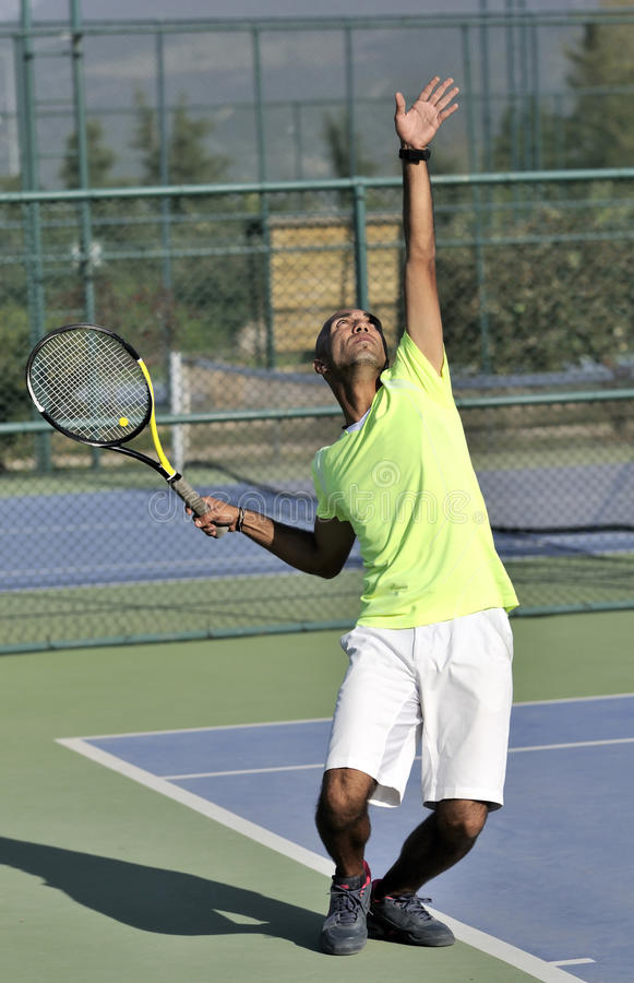 Serving a tennis ball. Into net. young man posing stock image