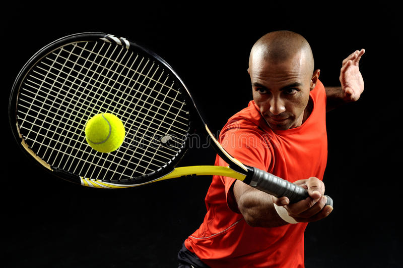 Serving a tennis ball. A portrait of a tanned sportive tennis player with a racket against black background stock photo