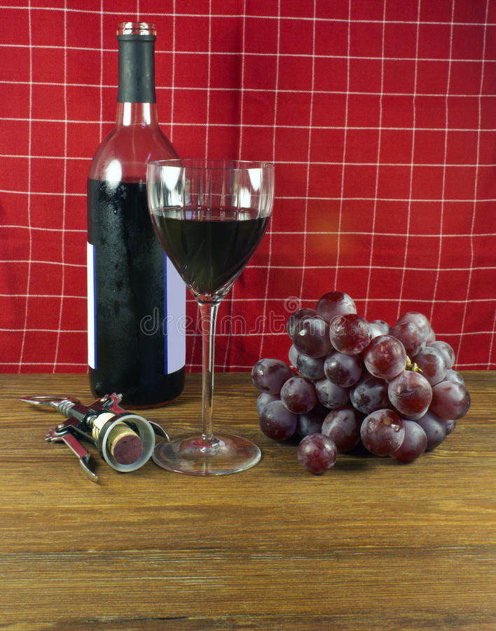 Serving wine. Wine bottle, glass and corkscrew with grapes on a wooden taable stock photography