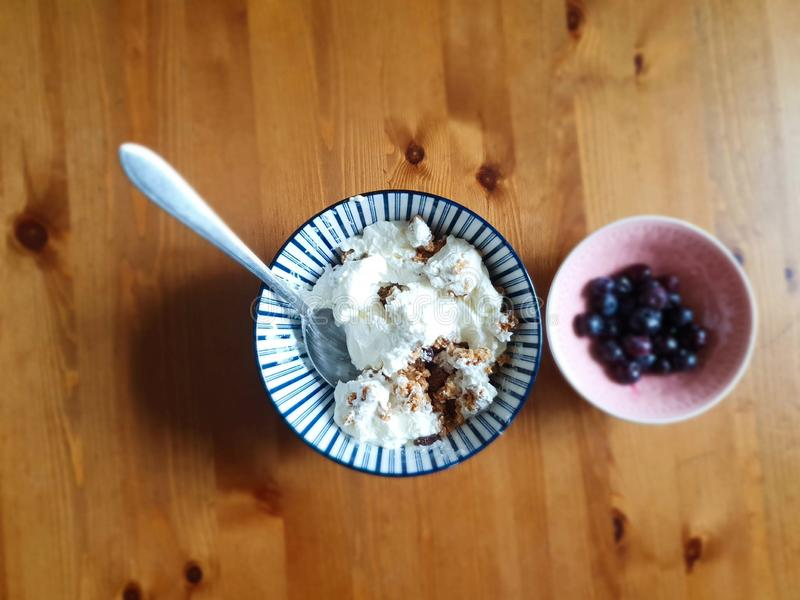 Serving of Yogurt with Whole Fresh Blueberries and Oatmeal on Old Rustic Wooden Table. Closeup Detail. breakfast in the royalty free stock photo