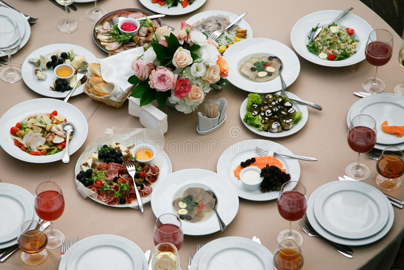 Servito per la tavola del ristorante di banchetto con i piatti, lo spuntino, la coltelleria, il vino ed i tubi di livello, alimen fotografia stock libera da diritti