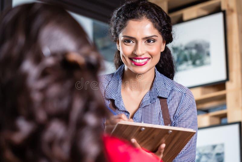 Servitris i den indiska restaurangen som tar beställningar royaltyfri fotografi