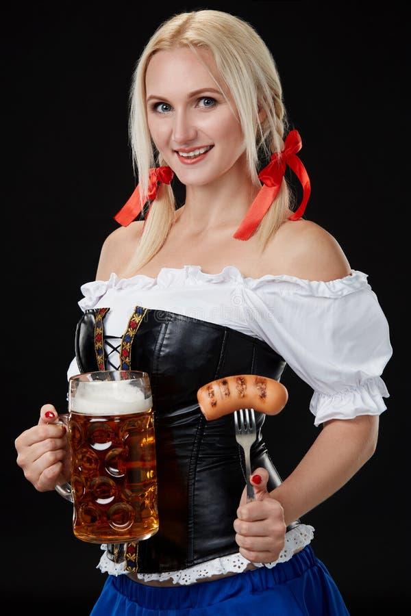 Servitris i hållande ölexponeringsglas för traditionell tysk dräkt på Oktoberfest royaltyfria foton