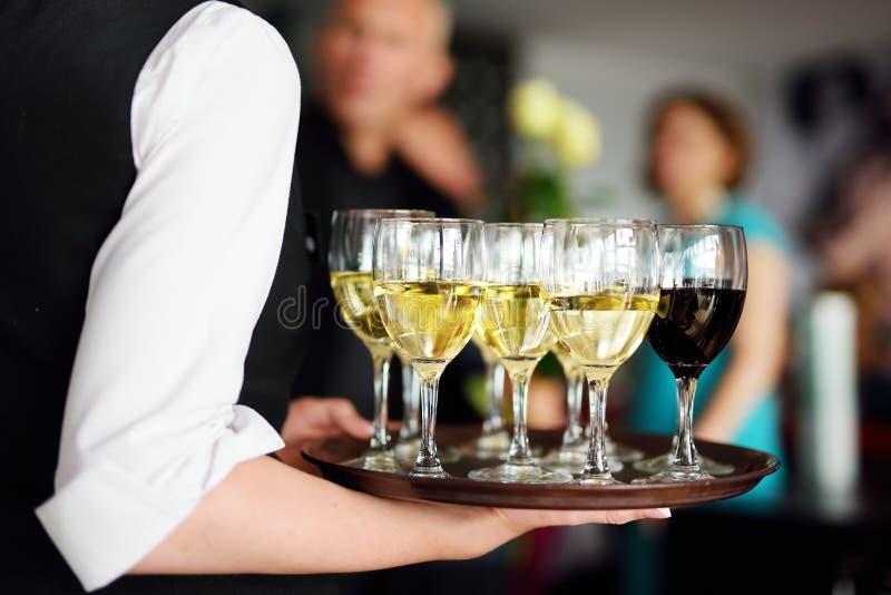Servitris med maträtten av champagne- och vinexponeringsglas arkivbild
