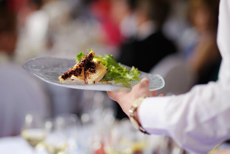 Servitris som bär en platta med meatmaträtten royaltyfri bild