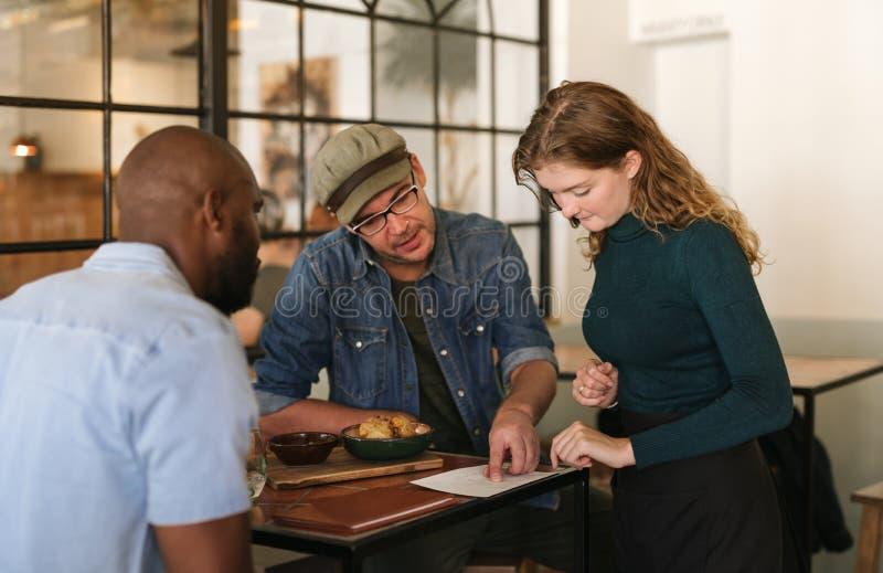 Servitris som förklarar menyn till kunder i en bistro arkivbilder