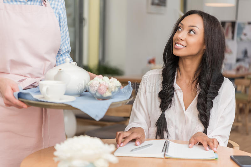 Servitris som kommer med te till ungt afrikansk amerikankvinnasammanträde royaltyfri fotografi