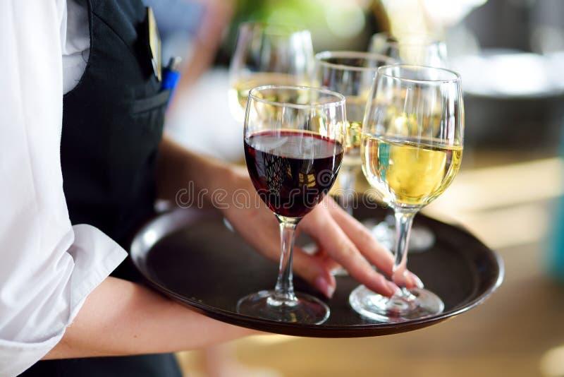 Servitris som rymmer en maträtt av champagne- och vinexponeringsglas på den festliga händelsen arkivbild