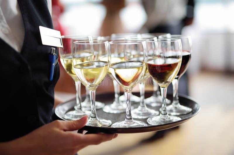 Servitris som rymmer en maträtt av champagne- och vinexponeringsglas på den festliga händelsen royaltyfri foto