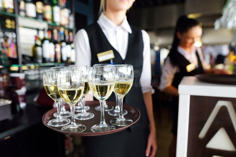 Servitris som rymmer en maträtt av champagne- och vinexponeringsglas på den festliga händelsen arkivfoton