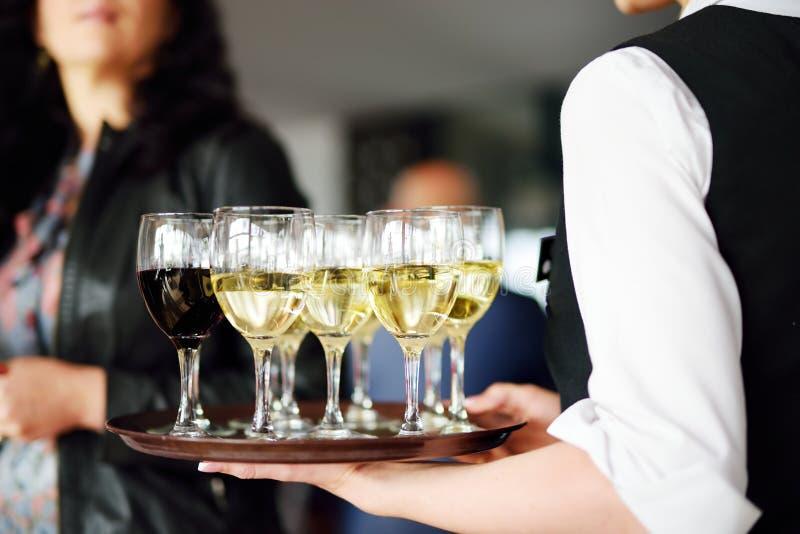 Servitris som rymmer en maträtt av champagne- och vinexponeringsglas på den festliga händelsen royaltyfri fotografi
