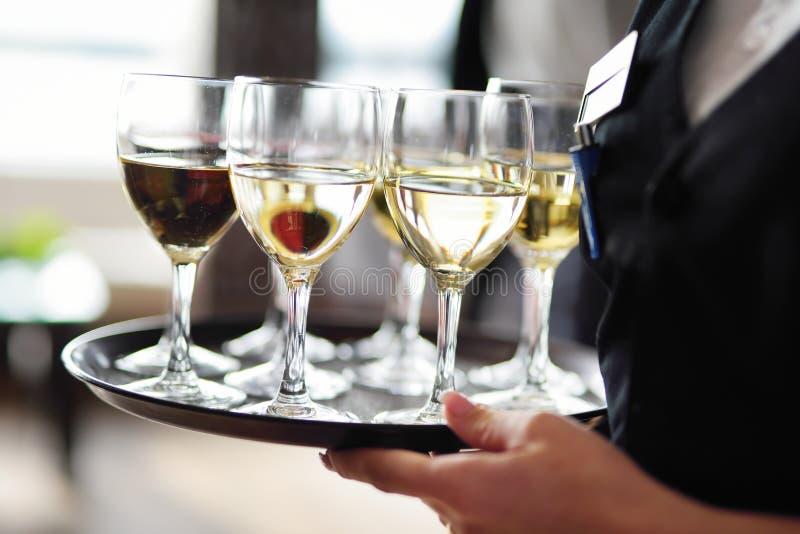 Servitris som rymmer en maträtt av champagne- och vinexponeringsglas på den festliga händelsen royaltyfria foton