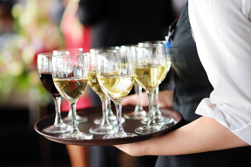 Servitris som rymmer en maträtt av champagne- och vinexponeringsglas på den festliga händelsen royaltyfri bild