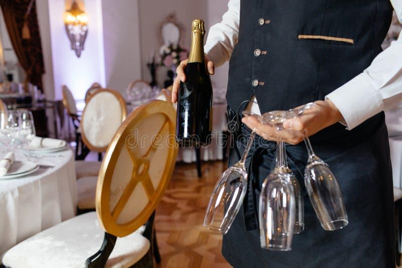 Servitris som rymmer en maträtt av champagne- och vinexponeringsglas på någon fe royaltyfri bild
