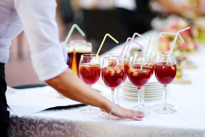 Servitris som rymmer en maträtt av sangriaexponeringsglas på någon festlig händelse royaltyfri fotografi