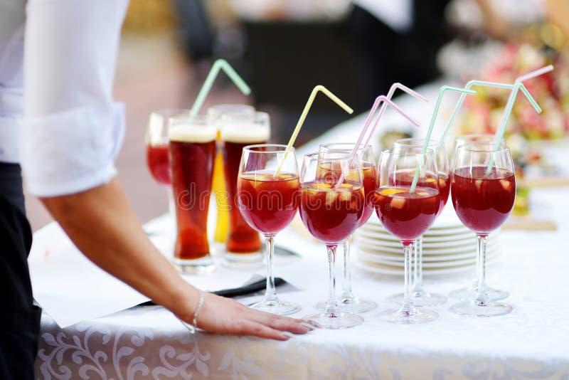 Servitris som rymmer en maträtt av sangriaexponeringsglas på någon festlig händelse royaltyfria foton