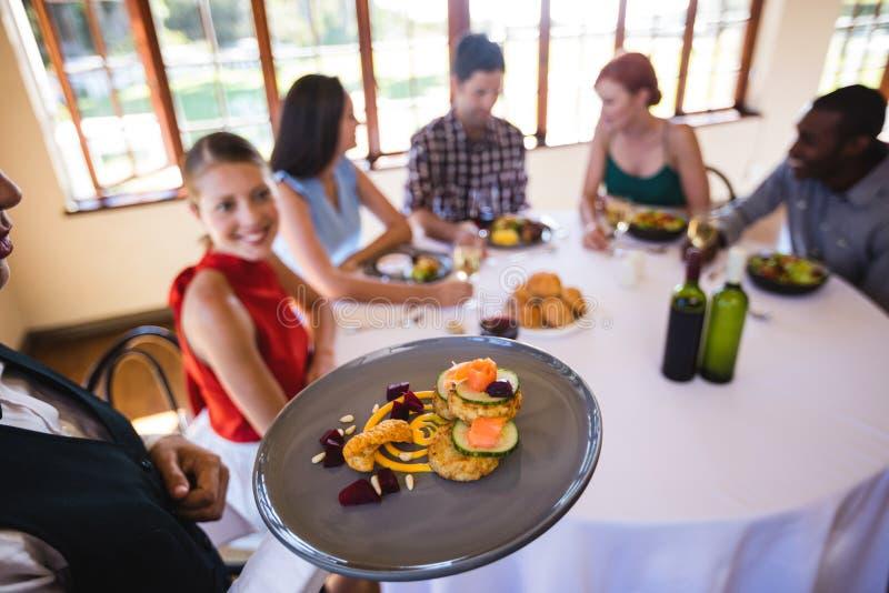Servitris som rymmer mat på plattan i restaurang arkivbilder