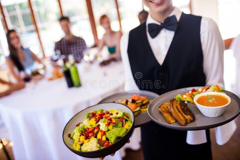 Servitris som rymmer mat på plattan i restaurang royaltyfri bild