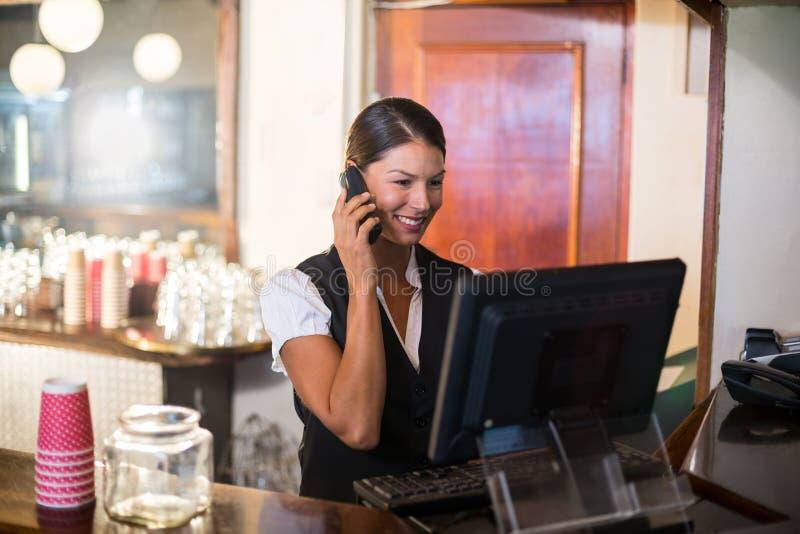 Servitris som talar på en telefon på räknaren arkivfoto