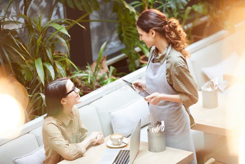 Servitris som talar till den unga kunden i kafé royaltyfri bild