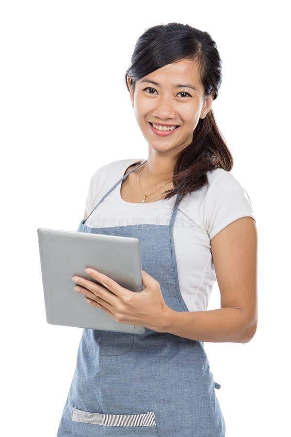 Servitris som tar en beställning genom att använda minnestavlaPC arkivfoto