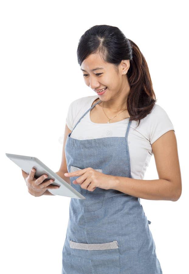 Servitris som tar en beställning genom att använda minnestavlaPC royaltyfria bilder