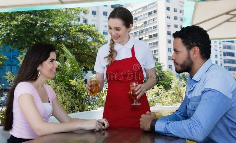 Servitris som tjänar som kallt öl till ett förälskelseparställe på restaurangen arkivfoto