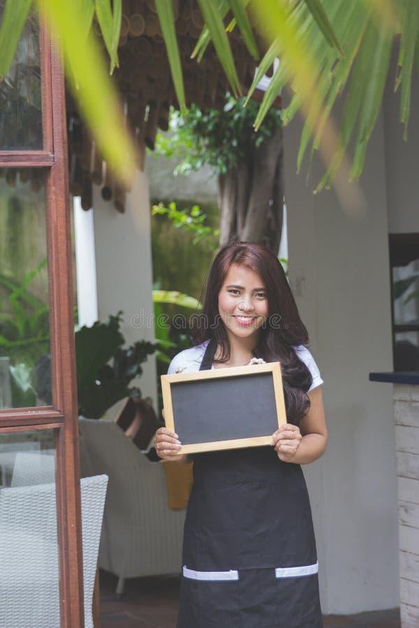 Servitrisanseende på framdelen av ett inviterande folk för kafé som kommer royaltyfri bild