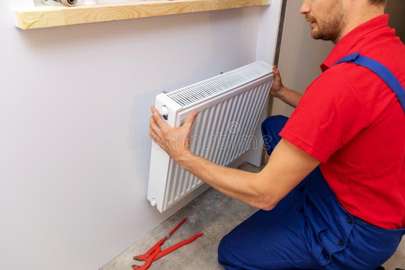 Servizi dell'impianto idraulico - idraulico che installa il radiatore del riscaldamento su w fotografie stock libere da diritti