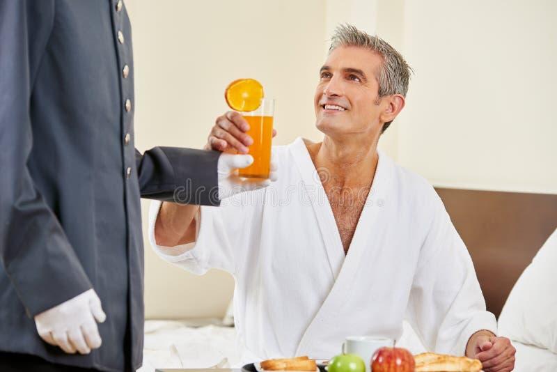Servizio in camera che porta prima colazione con succo d'arancia fotografie stock libere da diritti