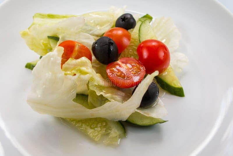 Servizio del ristorante, lattuga, cetrioli, olive, pomodori e salsa dell'olio d'oliva, primo piano immagini stock