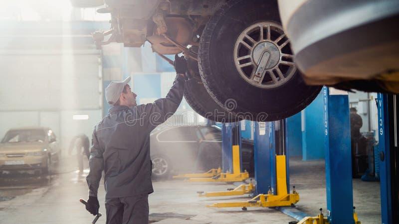 Servizio dell'automobile del garage - un meccanico controlla la trasmissione immagini stock libere da diritti