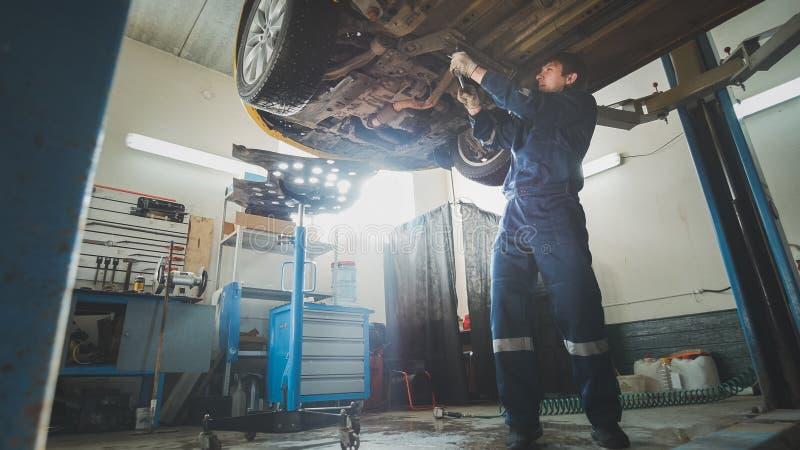 Servizio dell'automobile - un meccanico controlla la sospensione dell'automobile, grandangolare fotografia stock