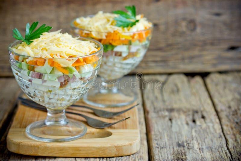 Servizio dell'insalata in vetro dal raccordo, dall'uovo, dal cetriolo, dalla carota, dalla patata e dal formaggio del pollo fotografia stock