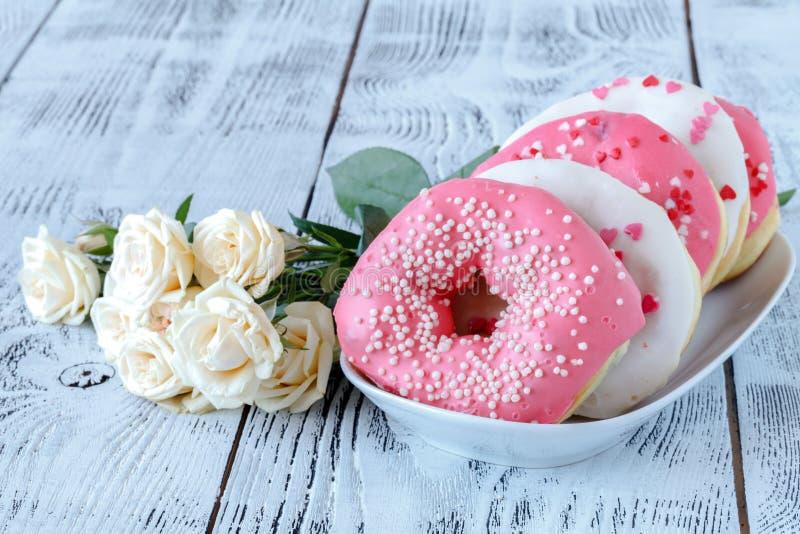Servizio della prima colazione di giorno di biglietti di S. Valentino con le rose bianche e la ciambella immagine stock