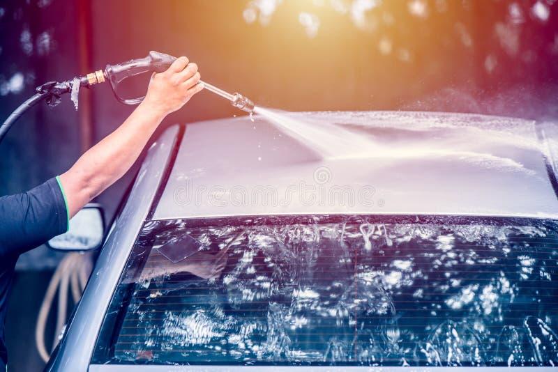 Servizio di cura di automobile facendo uso della pistola del getto di acqua alla pulizia fotografie stock
