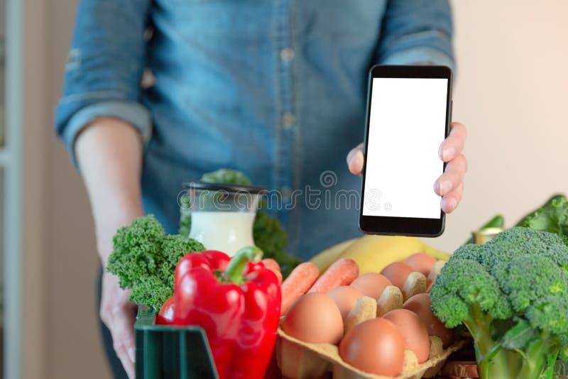 Servizio di distribuzione dell'alimento - smartphone della tenuta della donna davanti alla scatola di drogherie immagine stock libera da diritti