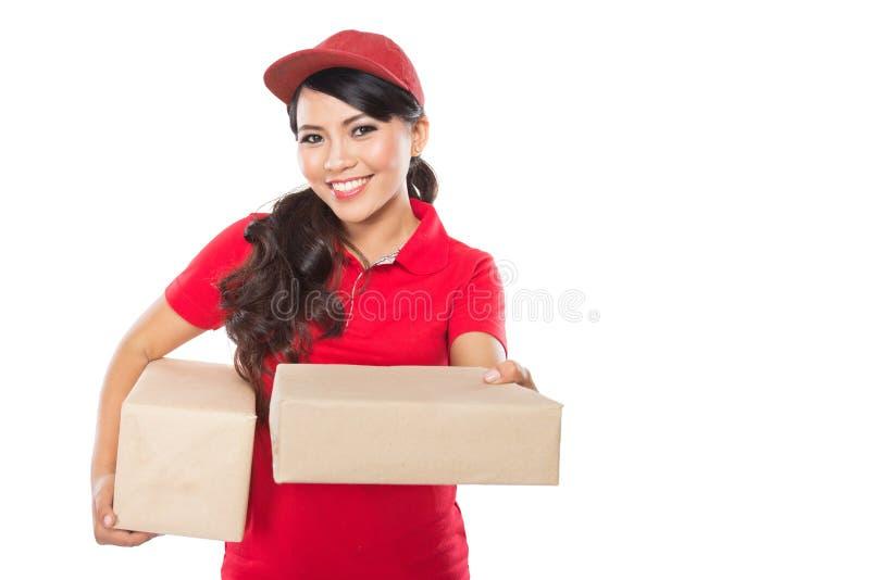 Servizio di distribuzione femminile che consegna felicemente pacchetto al costume fotografia stock