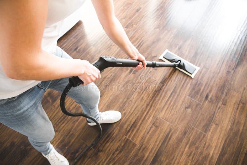 Servizio di pulizia domestico professionale La donna lava il pavimento con una zazzera del vapore immagini stock