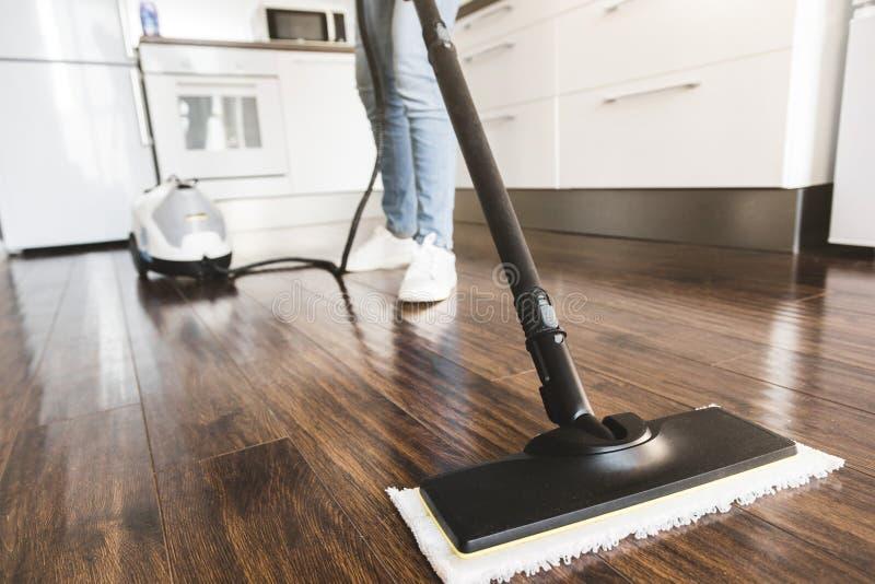 Servizio di pulizia domestico professionale La donna lava il pavimento con una zazzera del vapore fotografie stock libere da diritti