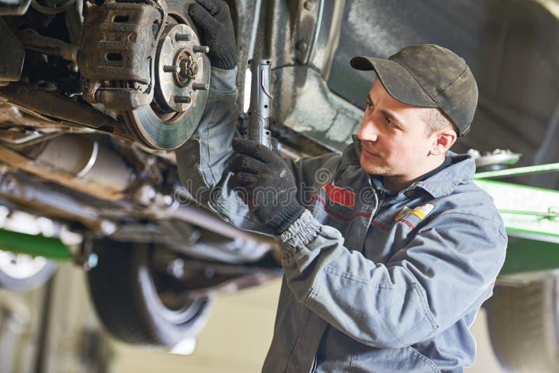 Servizio di riparazione automatica Meccanico che ispeziona la sospensione dell'automobile fotografie stock