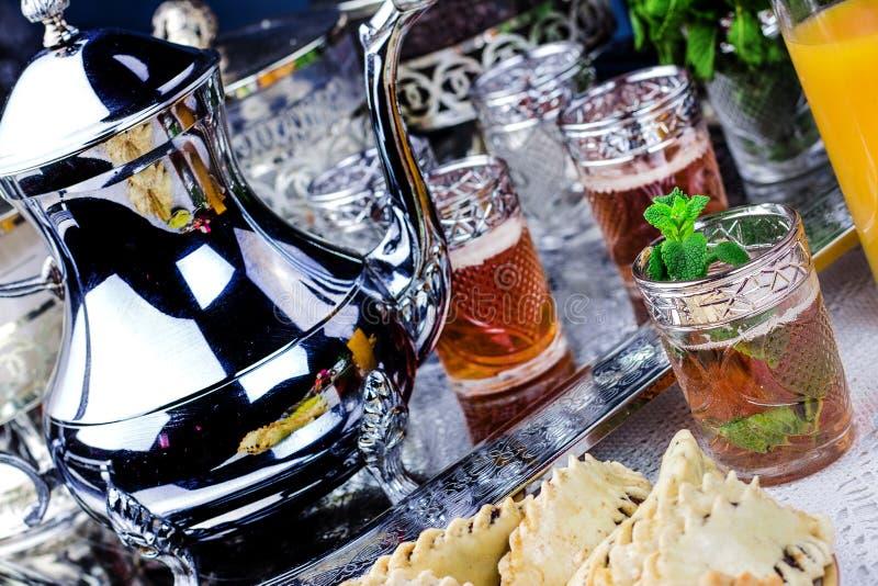 Servizio di tè d'argento del tè e dei biscotti marocchini della menta fotografia stock