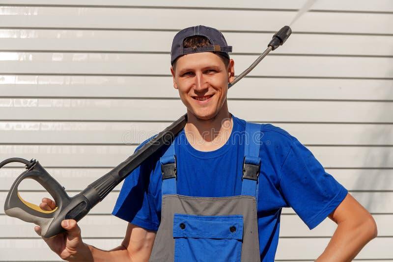 Servizio eliminante del lavoratore in berretto da baseball e camici Lavare le case e le facciate immagini stock