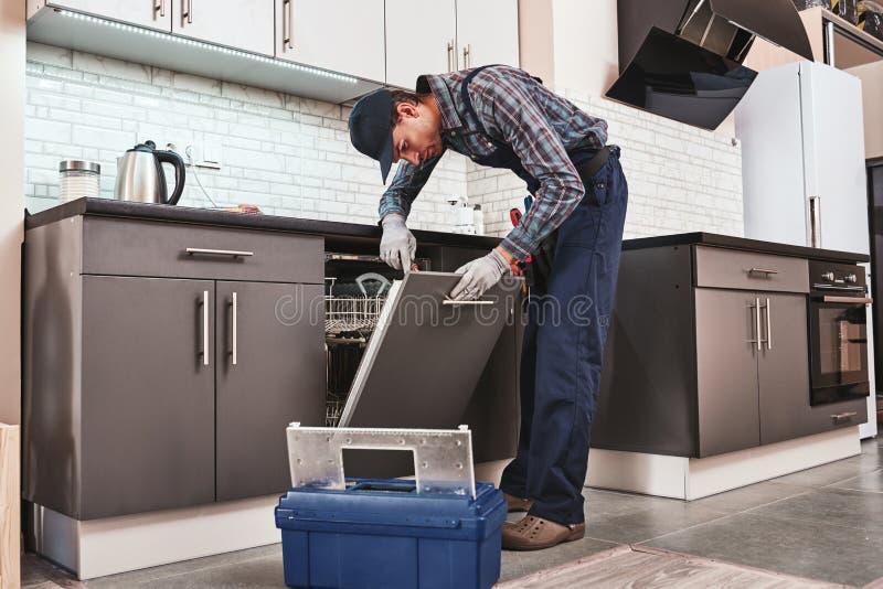 Servizio a tempo Tecnico maschio che si siede vicino alla lavastoviglie fotografia stock