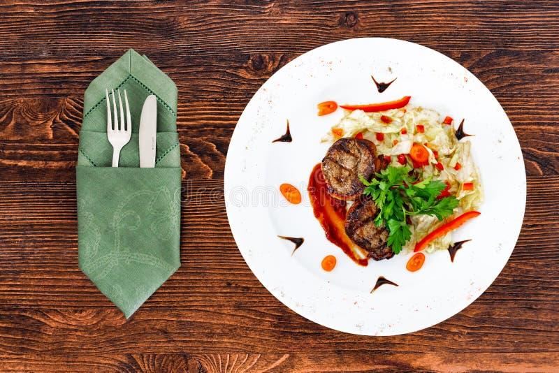 Servo succoso della bistecca da manzo raro medio con una salsa su un piatto bianco con gli apparecchi fotografia stock libera da diritti