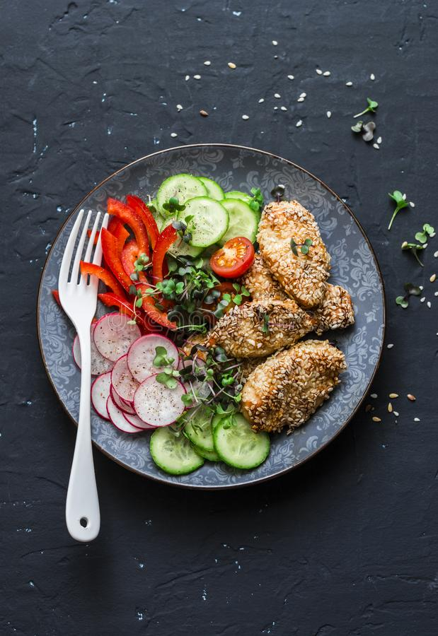 Sesame breading teriyaki baked chicken breast and fresh vegetables. Baked chicken and tomatoes, cucumbers, peppers, radishes, micr stock photos