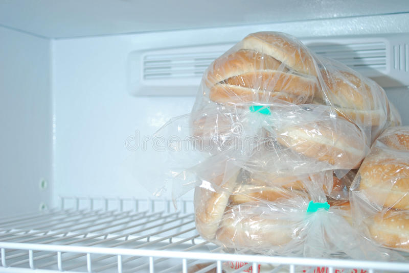 Sesame Hamburger buns. Hamburger buns topped with sesame seeds on a freezer shelf with the other half empty royalty free stock image