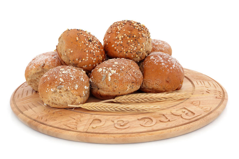 Sesame and Oat Bread Rolls. On a beech wood bread board with ears of wheat over white background royalty free stock photos